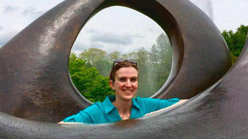 Svetlana in a teal shirt standing between two sculptures resembling eyes.