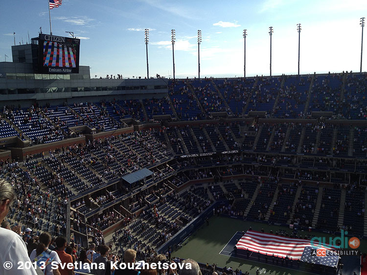 Tennis stadium showing a large screen, a scoreboard with open captions, an American flag.