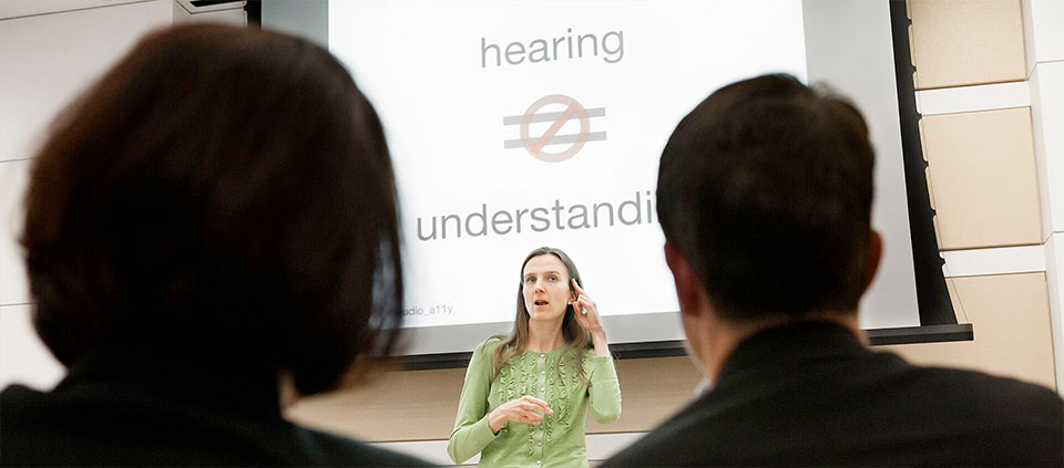 A woman in a green top signing cochlear implant in front of two audience members with their heads back to the image viewer. Behind her is a slide saying hearing is not equal to understanding.
