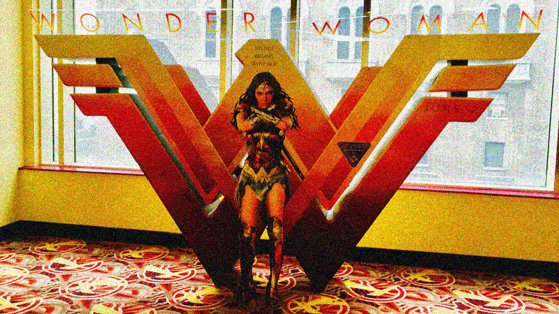 Cardboard display of W logo and Gal Gadot as Wonder Woman in front of it.