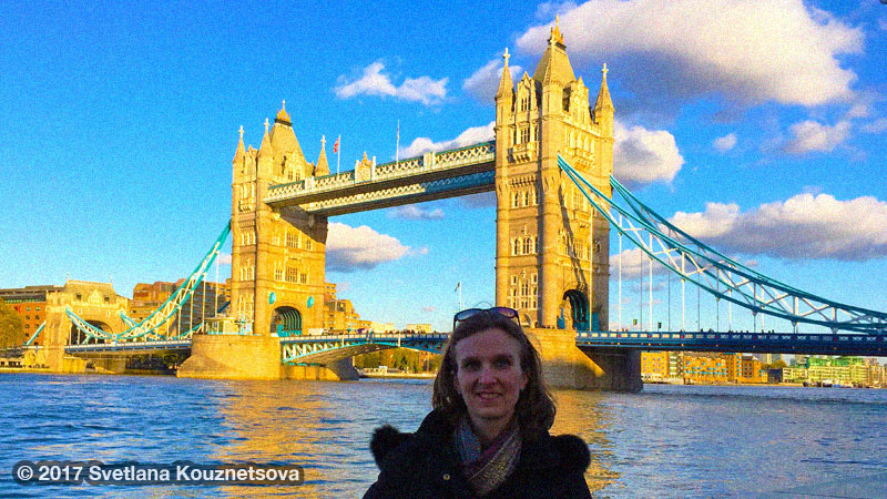 Sveta wearing a black down coat and standing in front of Tower Bridge in London on a sunny day