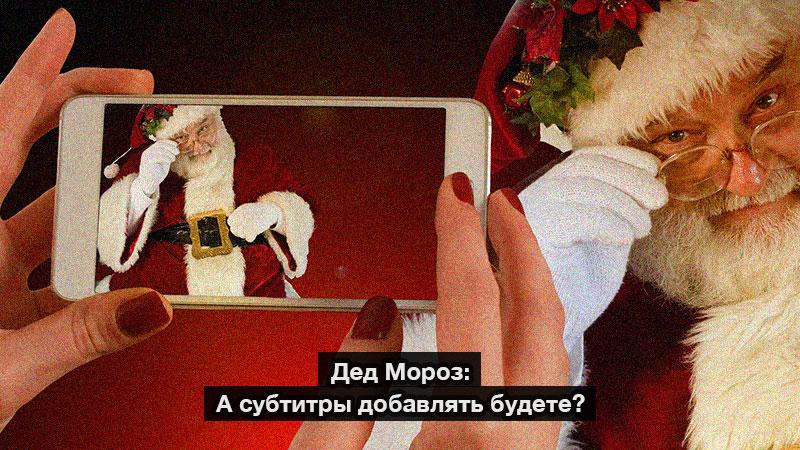 Женские руки держат айфон, снимая Деда Мороза на камеру. Впереди белые буквы на черной полоске - Дед Мороз: А субтитры добавлять будете?