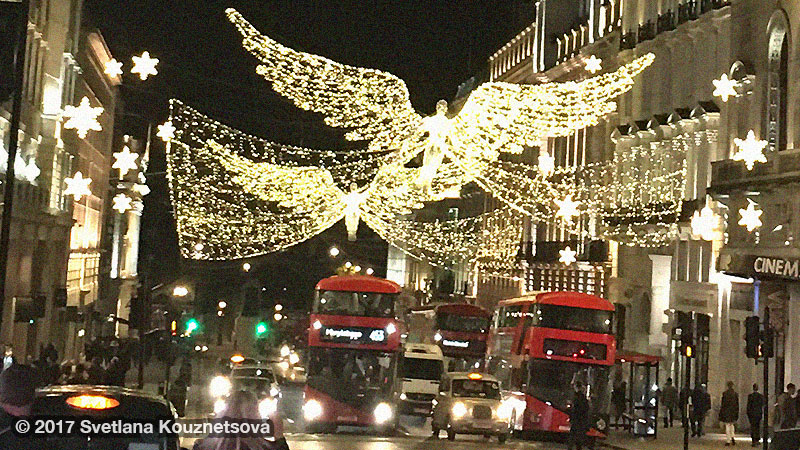 Night street of London with decorations of big angels above.